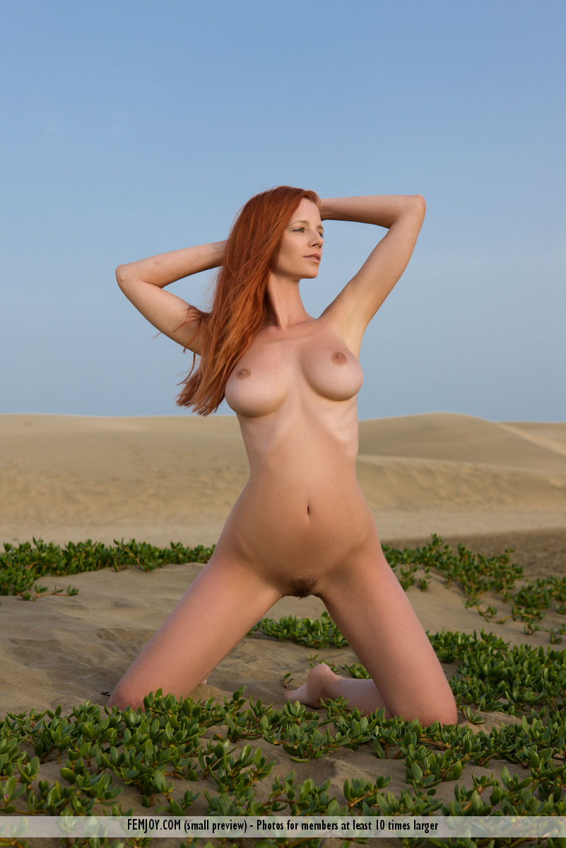 naked redhead lady lying naked in the desert sand busty