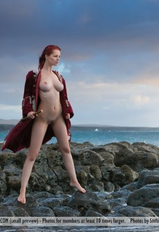Nude Woman Standing On A Rocky Coast Line